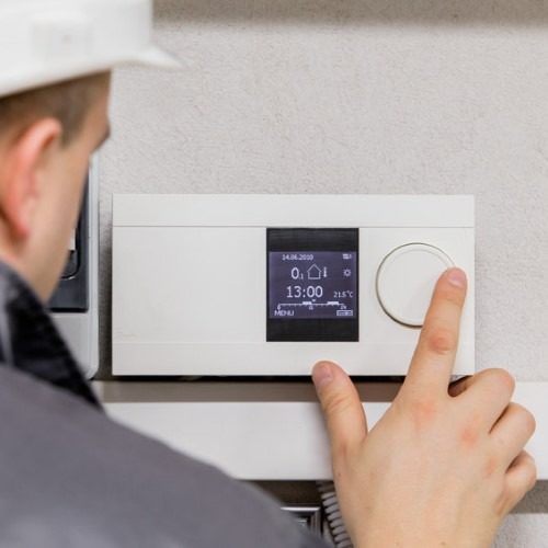 Engineer adjusting thermostat for efficient automated heating system
